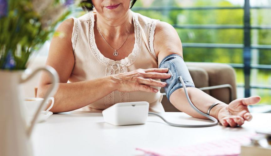 Измерение артериального давления тонометром. Женщина меряет давление