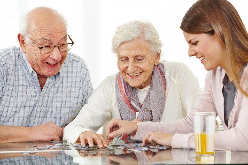 пожилые люди собирают паззл